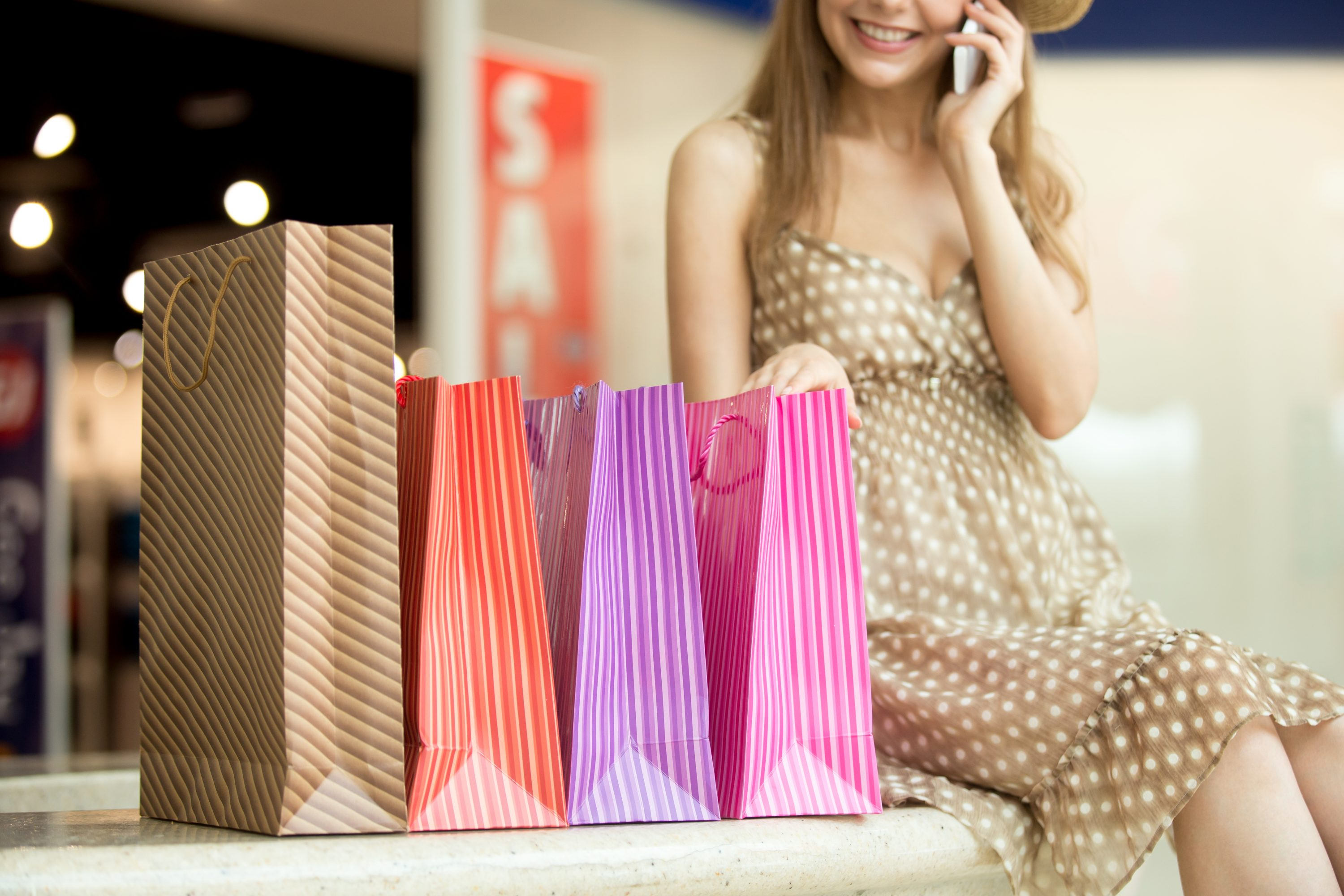 Close-up of beautiful smiling young shopper woman sitting with shopping paper bags talking on phone, making call. Focus on bags. Fashion, sale, shopping concept. Sale sign on background